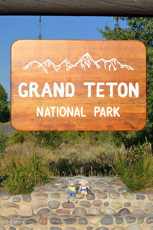 Mo und Mona am Schild des Grand Teton National Park